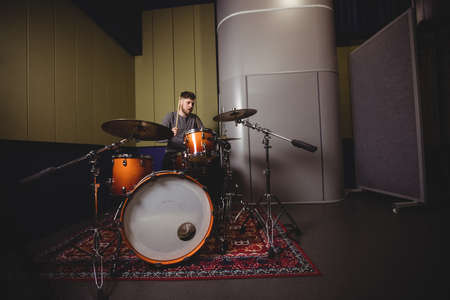 drum set: Male student playing drum set in a studio