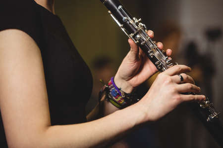 clarinete: Mid-section of female student playing clarinet in a studio
