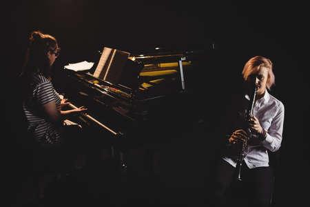 clarinete: Dos estudiantes de sexo femenino que juegan clarinete y piano en un estudio