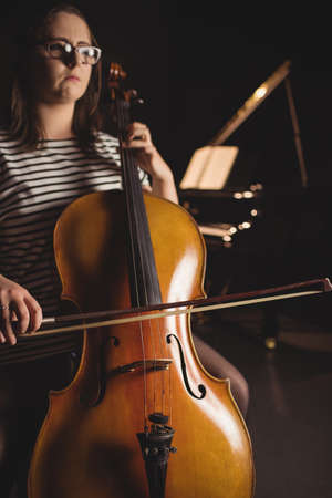 Female student playing double bass in a studio