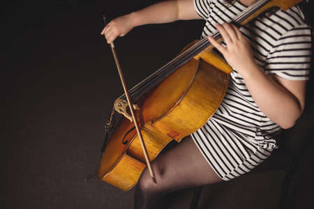 Mid-section of female student playing double bass in a studio