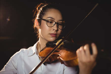 Female student playing violin in a studio LANG_EVOIMAGES