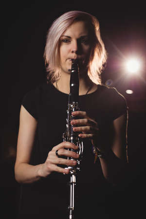 clarinete: Female student playing clarinet in a studio