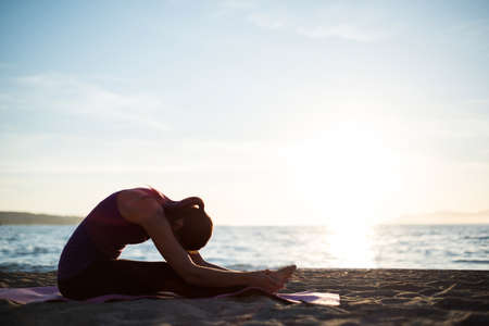 janu: Woman performing yoga on beach on a sunny day