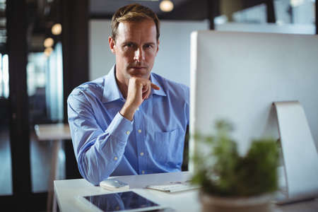 technology: Portrait of businessman using desktop pc in office