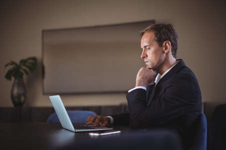 strong chin: Thoughtful Business man using laptop at desk in office