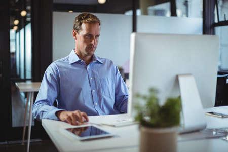 Businessman using desktop pc in office