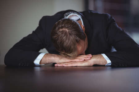 head down: Exhausted businessman sitting with his head down on office desk