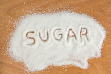 sugar powder: Close-up of sugar written on sugar powder on table Stock Photo