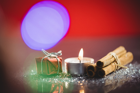 Cinnamon stick, lit candle and gift during christmas time