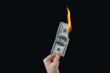 hundred dollar bill: Hand holding hundred dollar bill on fire against black background Stock Photo