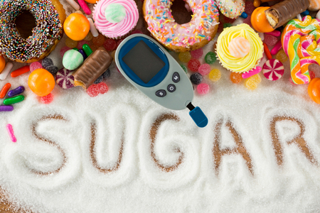 diabetes meter kit: Various types of doughnuts and cupcakes with glucometer on wooden table