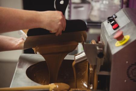 Werknemer het vullen van vorm met gesmolten chocolade in de keuken
