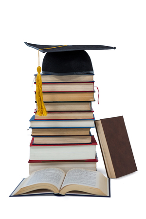 mortarboard: Mortarboard on stack of books on white background Stock Photo