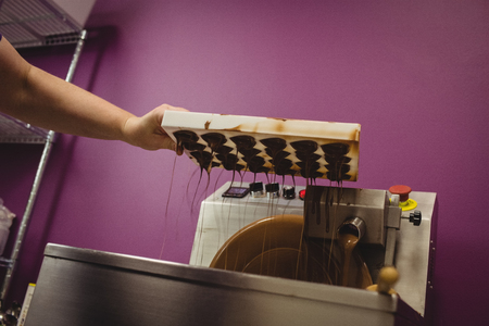 Worker pouring melted chocolate in blending machine at factory
