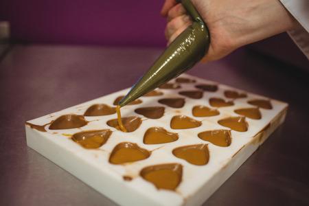 molde llenando Trabajador con la manga pastelera en la cocina