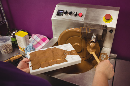 mould: Worker filling mould with melted chocolate in kitchen