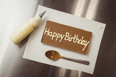 cake factory: Happy birthday written on chocolate plaque in kitchen Stock Photo