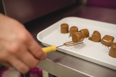 cake factory: Worker arranging chocolate coated marshmallows on tray in kitchen