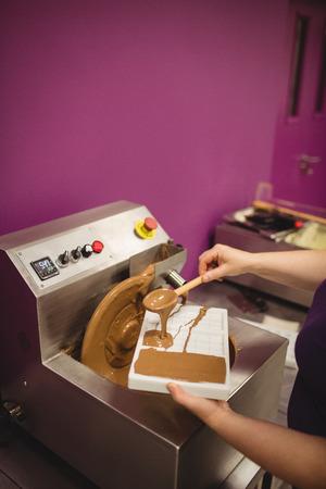 chocolatería: Mediados de sección de molde llenando trabajador con chocolate derretido en la cocina