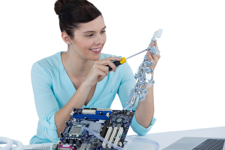 Female computer engineer repairing computer motherboard against white background