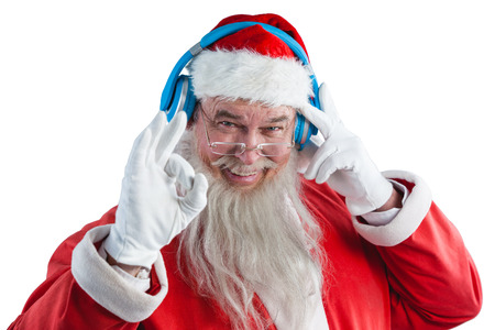 Happy santa claus showing hand okay sign while listening to music on headphones
