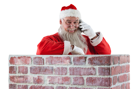 Santa claus standing beside chimney and talking on mobile phone against white background