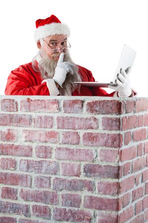gesturing: Santa claus with finger on lips while using laptop against white background