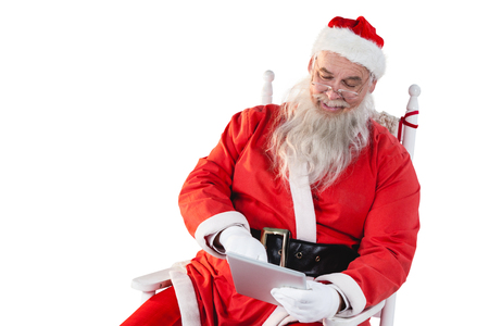 Santa claus using digital tablet against white background Stock Photo