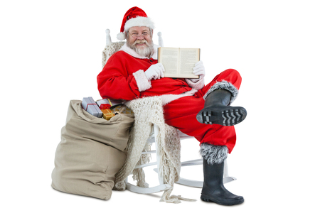 Santa claus showing bible with sack of christmas present beside him against white background
