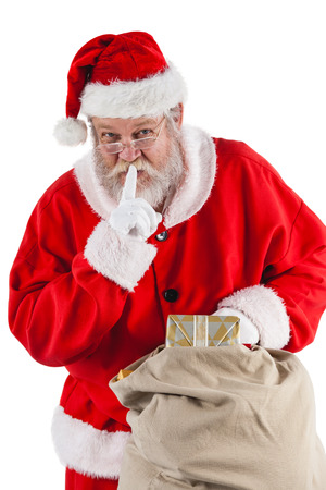 Santa claus with finger on lips and holding a gifts against white background Stock Photo