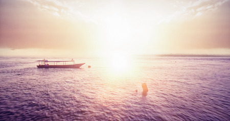 adventuring: Sunset over a bay with fishing boat Stock Photo
