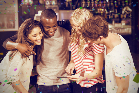 Happy friends looking at smartphone against flying colours