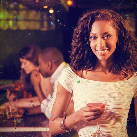 socializando: Retrato de mujer joven con un cóctel en la barra contraria contra los colores de vuelo