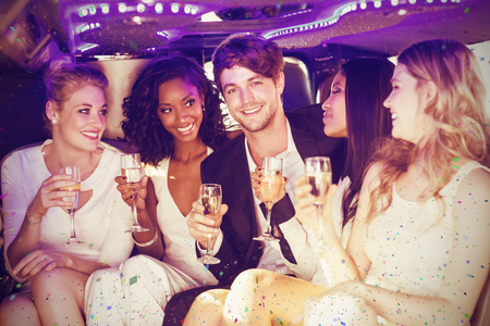 half dressed: Happy friends drinking champagne while sitting against flying colours