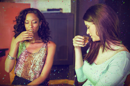 Two women having tequila against flying colours