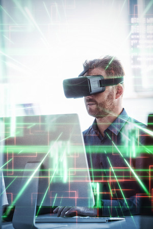 virtual reality simulator: Green and red lines next to screens against businessman using virtual reality simulator while working on computer Stock Photo