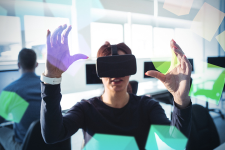 virtual reality simulator: Digitally generated grey cubes floating  against businesswoman with virtual reality simulator Stock Photo