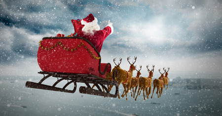 Santa Claus riding on sleigh during Christmas against coastline and city