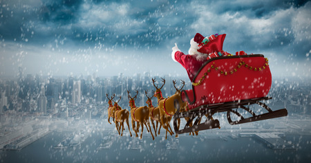 Santa Claus riding on sleigh with gift box against coastline and city