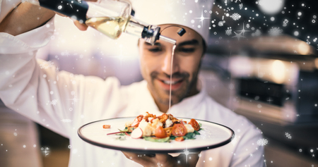Snow falling against handsome chef pouring olive oil on meal