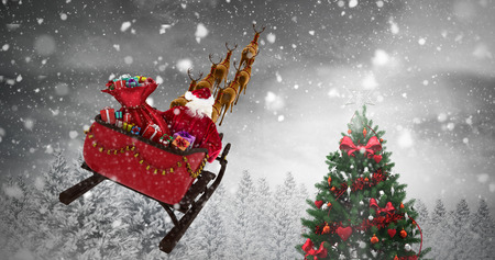 High angle view of Santa Claus riding on sled during Christmas against christmas tree in snowy forest Stock Photo