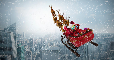 High angle view of Santa Claus riding on sled with gift box against cityscape