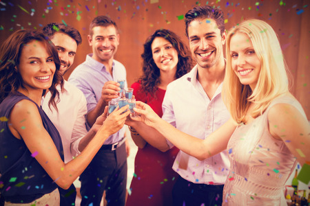 Portrait of friends drinking shots while standing together against flying colours