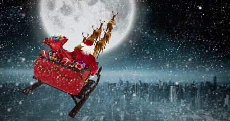 High angle view of Santa Claus riding on sled during Christmas against balcony overlooking city Stock Photo