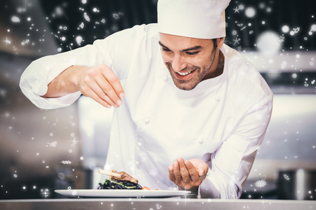 sprinkling: Snow falling against chef sprinkling spices on dish