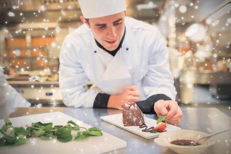 Snow falling against cheerful chef putting mint with his dessert Stock Photo