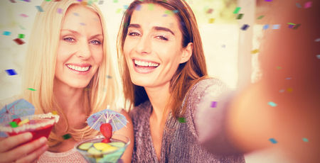 non alcoholic beverage: Beautiful women taking selfie with mobile phone against flying colours
