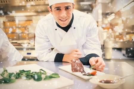 Snow falling against smiling chef putting mint with his dessert Stock Photo