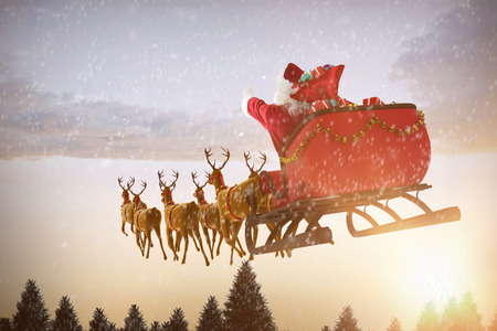 Santa Claus riding on sleigh with gift box against snow falling on fir tree forest Stock Photo